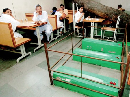 Customers wait for their orders next to graves inside Lucky Cafe in Ahmedabad.